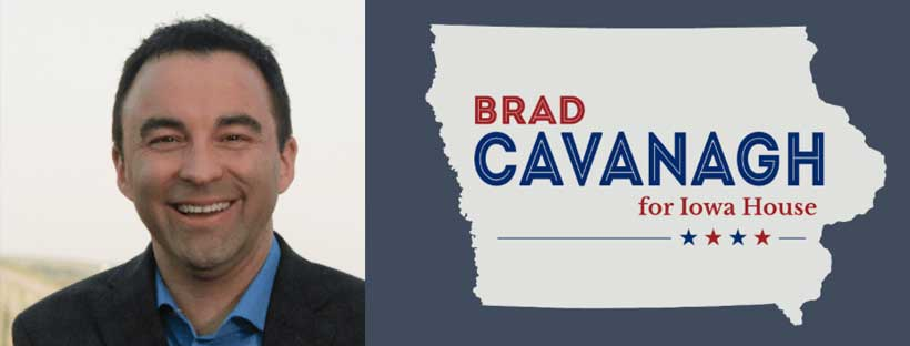 Man with short dark hair, blue shirt and dark blazer next to Campaign Logo in the shape of Iowa