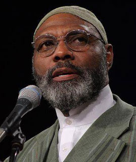 Man with grayish short, round, brimless cap, round glasses, short black beard with hints of white on the corners of his chin, white shirt with high collar buttoned on the neck, and a grayish coat, before a microphone