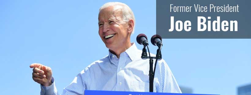 Joe Biden smiling and pointing before a blue sky