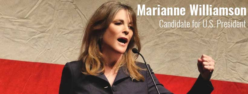 Marianne Williamson speaking before U.S. Flag